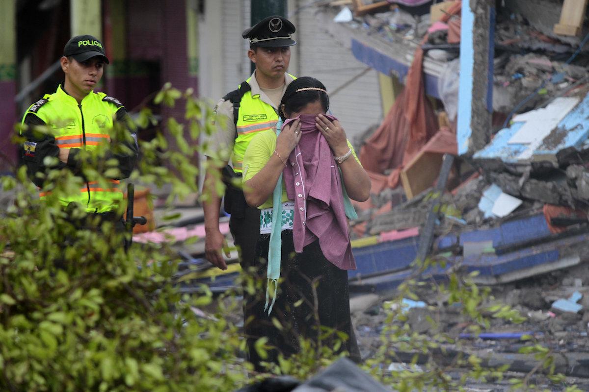 GRA236. PEDERNALES (ECUADOR) 17/04/2016.- Policía y habitantes de Pedernales (Ecuador), afectado por el terremoto de 7,8 grados en la escala de Richter registrado el sábado en la costa norte de Ecuador, caminan entre las casas destruidas y los escombros. Esta ciudad turística, un popular balneario de la costa ecuatoriana, es hoy el epicentro de una tragedia por la que al menos 77 personas murieron y 588 resultaron heridas. EFE/José Jácome